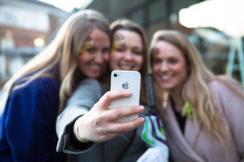 Three people taking a selfie on an iPhone