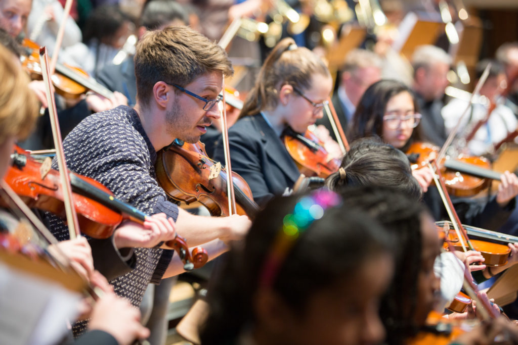 A member of the London Chamber Orchestra rehearsing with young string players.