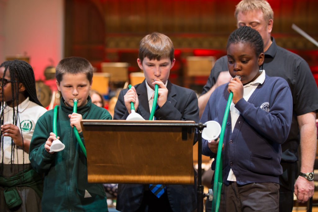 Three student participants of LCO's Music Junction programme playing toy horns in the Toy Symphony.
