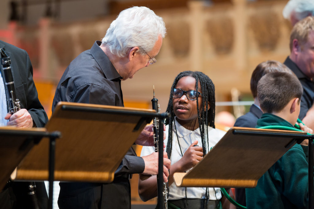 A young student participant of the LCO's Music Junction programme talks to one of the orchestra's oboists.